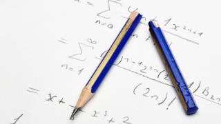 lápiz roto sobre hoja con álgebra