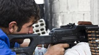 A member of the Kurdish People's Protection Units (YPG) holds a position with his weapon in Kobane (19 November 2014)