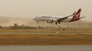 A plane lands at Canberra Airport amid thick bushfire smoke