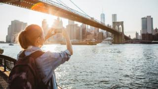 Woman takes photo of New York City skyline