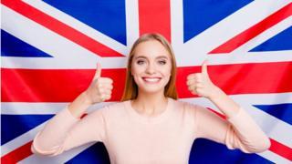 Женщина на фоне британского флага.
