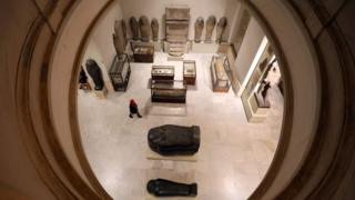 A visitor walks near artefacts inside the Egyptian Museum in Cairo, Egypt November 15, 2017.