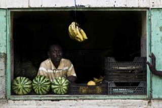 A fruit seller stands in front of his shop window with crates of fruit visible next and behind him