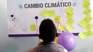 Niño mira un cartel sobre cambio climático