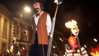 a guy being burned at bonfire night parade