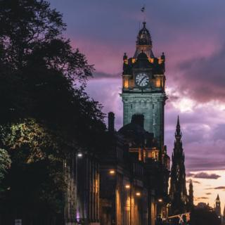 clock tower of the Balmoral Hotel in Edinburgh at sunset.