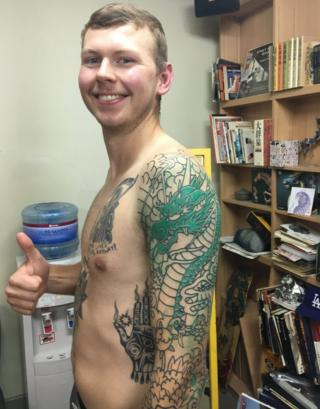 Kyle Seeley smiles and gives a thumbs-up while showing off his new dragon tattoo