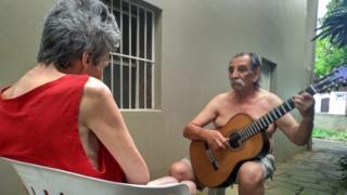 Lucio Yanel plays guitar to his wife Sueli