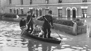 Policemen rowing down a street in the 1947 London floods