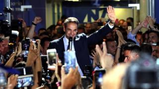 Kyriakos Mitsotakis waves with his left hand in the air while holding a microphone in the other, as a crowd clap and cheer and a media scrum swarms around with cameras