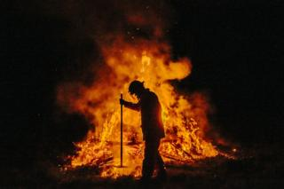 A firefighter, seen in silhouette, attends to a controlled fire with a rake