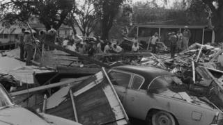 Local residents climb over destroyed cars and collapsed buildings after Hurricane Audrey hit Lousiana in June 1957