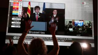 People watch Carles Puigdemont after Catalonia's regional election in Brussels, on a giant screen in Barcelona, Spain, December 21, 2017