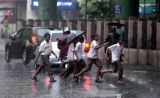 Indian school students cross the street under monsoon rains in Chennai