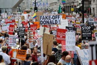 Protesters against the UK visit of US President Donald Trump gather with placards to take part in a march and rally in London