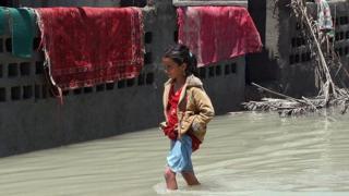 طفلة تمشي والمياه تقترب من ركبتيها