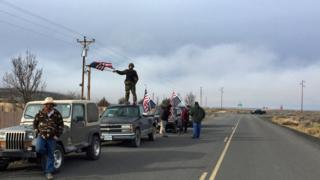 People wave US flags near the Malheur Refuge