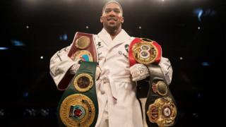 Anthony Joshua with im four belts