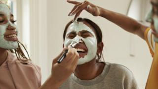 Young women apply face masks