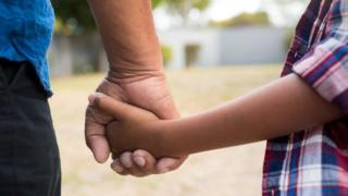 Close up child and adult hold hands