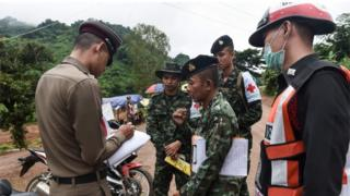 A Thai policeman speaks with a Thai soldier at the Tham Luang cave area on 8 July 2018.