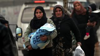 Syrian women carry children and bags in the Kurdish-controlled northern Syrian town of Manbij on 30 December 2018