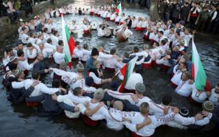 Men dance in the icy waters of Tundzha river during a celebration of Epiphany Day