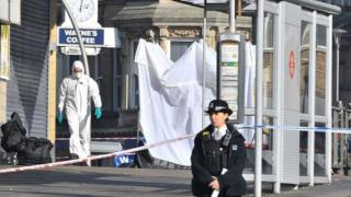 Police officer outside the scene of a stabbing at Ilford station