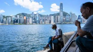 A man sits along the Kowloon side of Victoria Harbour which faces the skyline of Hong Kong Island.