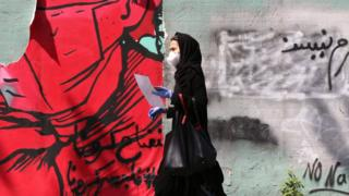 Northern Ireland A Iranian woman wearing a protective mask and gloves walks past a mask graffiti in Tehran