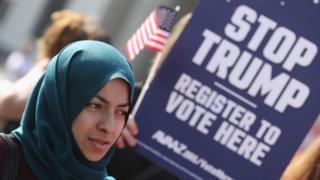 """Девушка в платке на фоне плаката """"останови Трампа"""""""