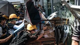 В обід група протестувальників розбила скляні двері будівлі за допомогою металевого візка