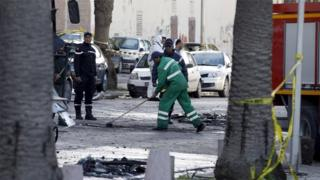 A sanitary service worker cleans the scene of a suicide bomb attack in Tunis