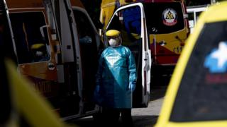 A Health worker waits in a protective suit among the ambulances at the Gregorio Mara?ón hospital on May 13, 2020 in Madrid, Spain