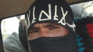 A close-up shot of an Islamist militant wearing a black veil which only shows his eyes