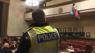 Cambridge City Council chamber and protesters and police
