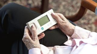 Elderly person using a device to test her heart rhythm