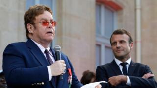 Mwanamuziki Elton John(kushoto) akipewa tuzo na Emmanuel Macron katika kasri ya rais