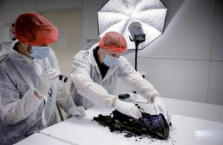 Investigators in protective clothing inspect the bag
