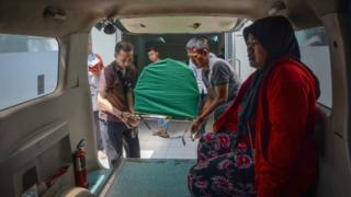 Body of a man who died from tainted alcohol is carried into an ambulance in Cicalengka