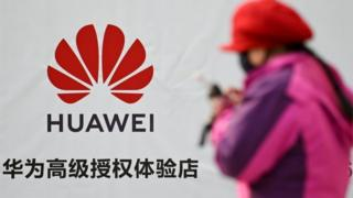 Woman next to Huawei sign