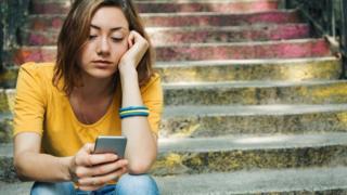 Девушка смотрит на телефон
