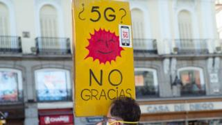 """A protester holding a yellow sign which says """"5G? No Gracias"""""""