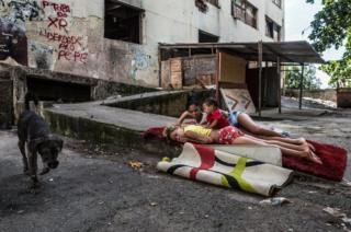Girls playing with a baby on a carpet in front of the abandoned IBGE building, 'Favela' Mangueira community, Rio de Janeiro, Brazil