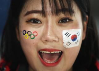 A South Korea fan smiles with logos on her face