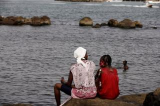 Women sit on a rock at a beach called