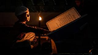 An Indonesian Muslim boy holds a torch while reading