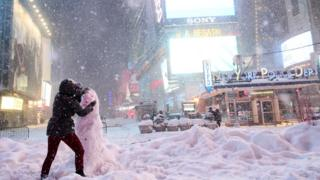 A woman decorates a snowman in Times Square in New York