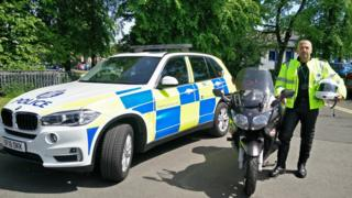 Police officer standing next to patrol car and motorbike
