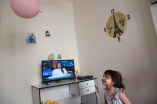 Fatima, 4, is playing with a balloon at her new home in Chania. Fatima is Ahmed's youngest daughter. On the background, the cable TV is showing the news from a Syrian TV channel.